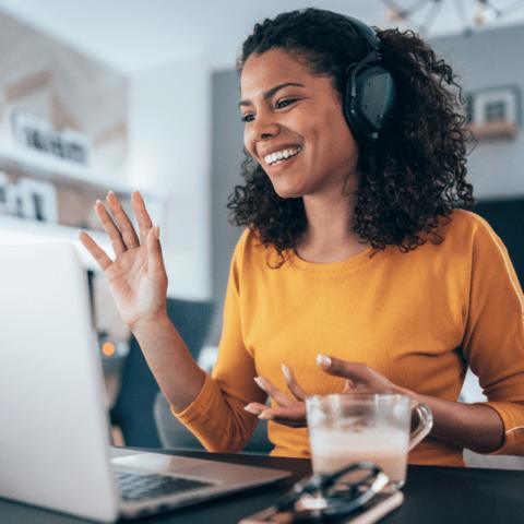 Woman wearing headphones and waving at a computer camera