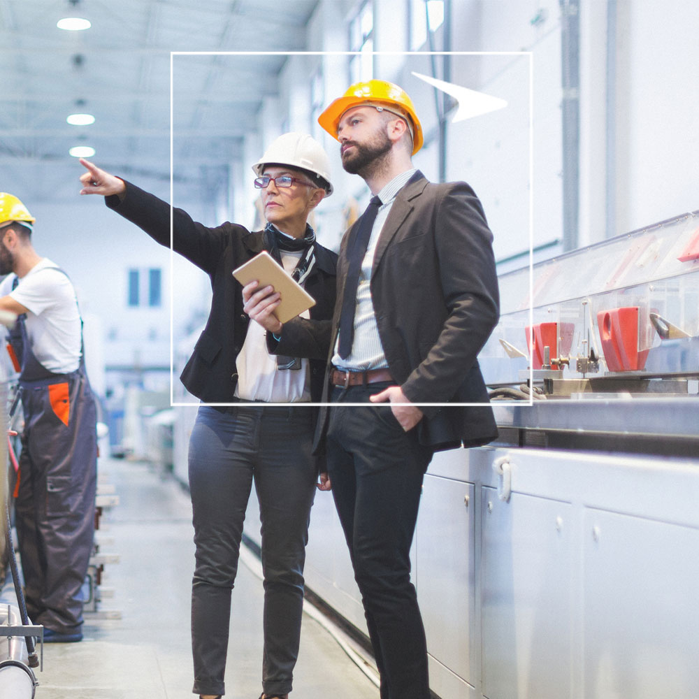 Two coworkers in hard hats and suits against warehouse background
