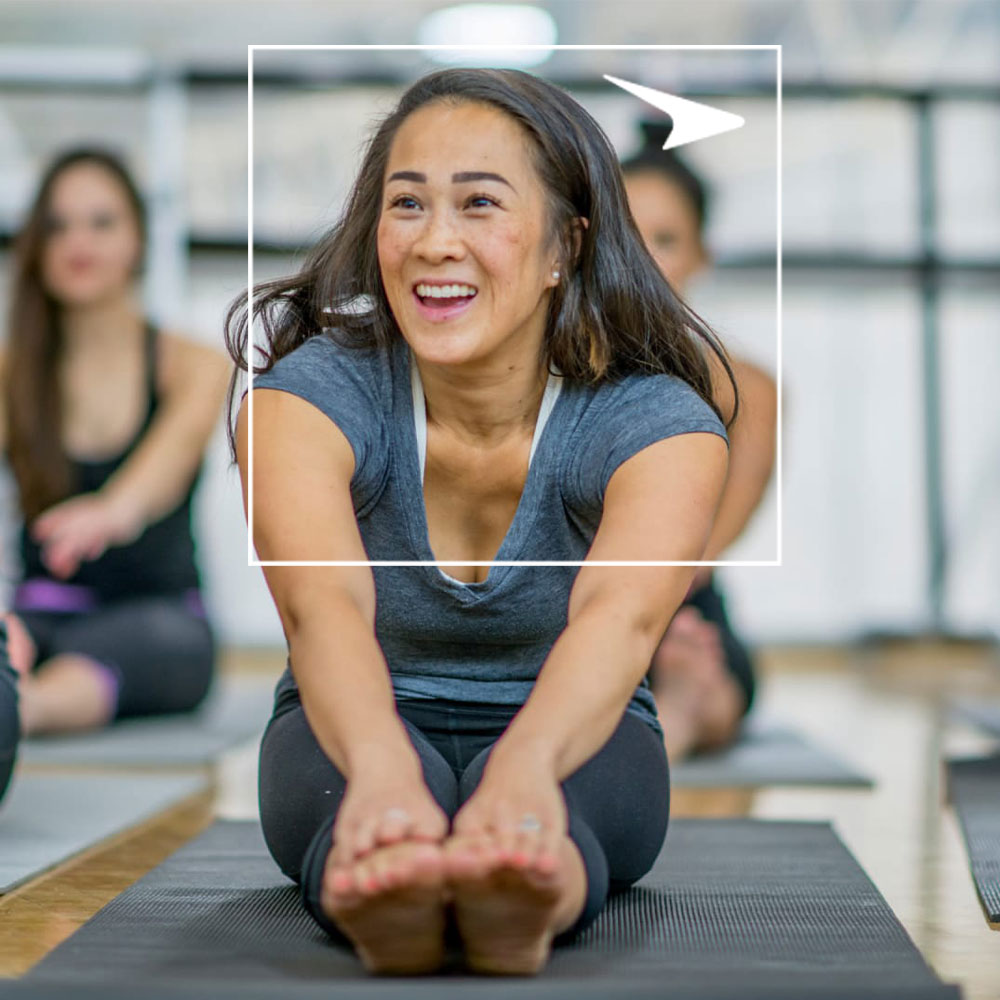 Woman stretching on yoga mat in workout class