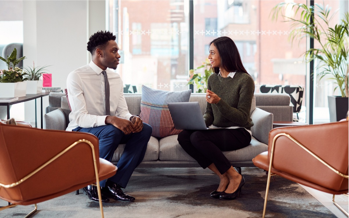 Woman with laptop computer interviewing man with suit on couch