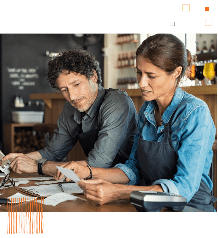 Man and woman looking over receipts with coffee shop background