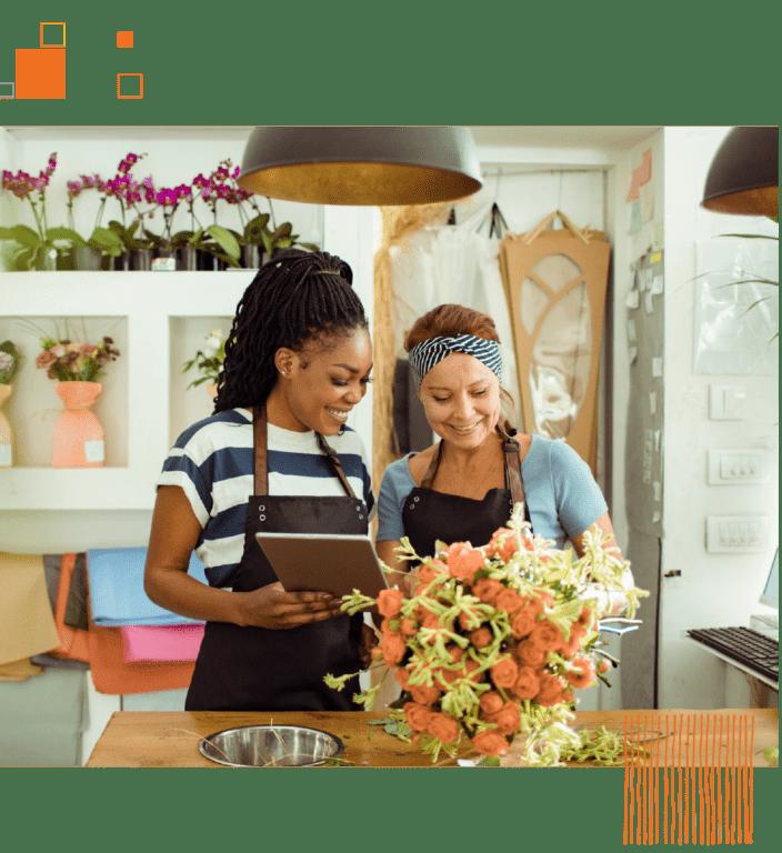 Two women in aprons making floral arrangement in flower shop