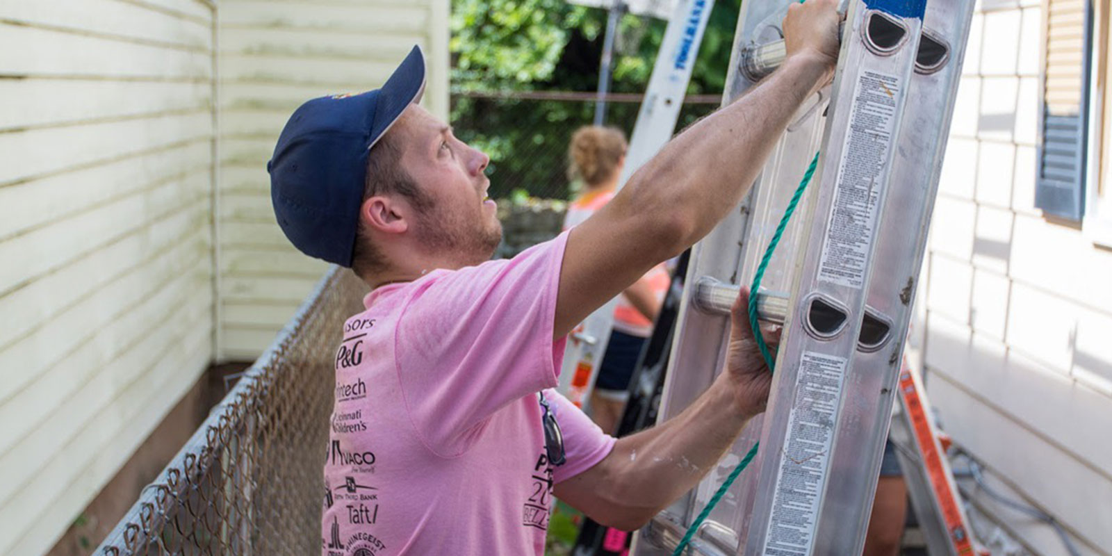 Paycor employee standing on ladder working for community service