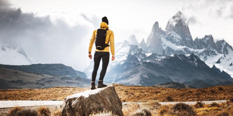 Man standing on a boulder in a mountainous terrain