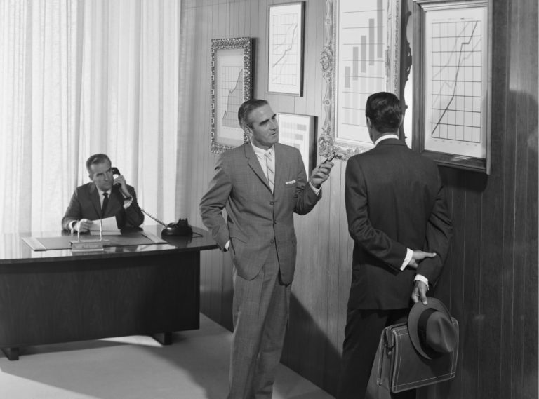 Three men in office looking at bar graphs with black and white effect