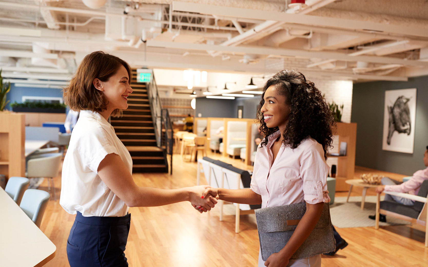Two coworkers shaking hands in bright office