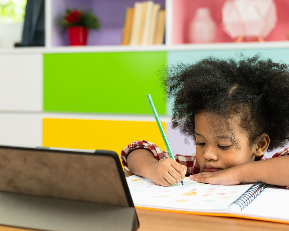 Little girl at desk drawing in coloring book