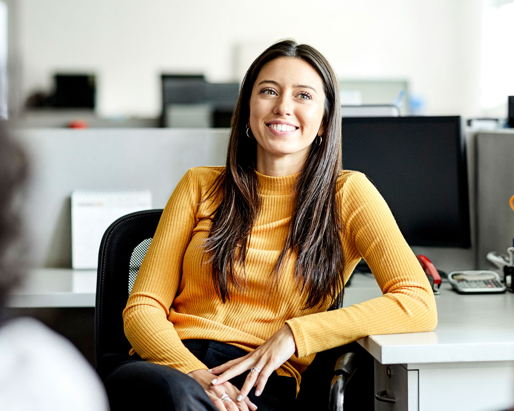 Woman sitting in cubicle smiling